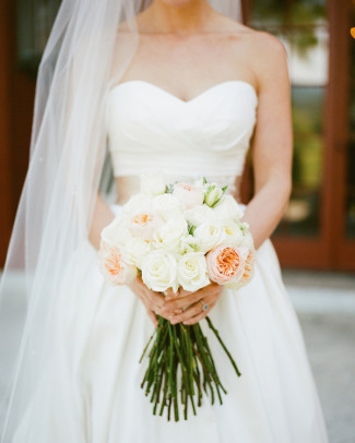 Bride wearing sweet heart neckline, wearing a veil and holding a blush pink and white bouquet