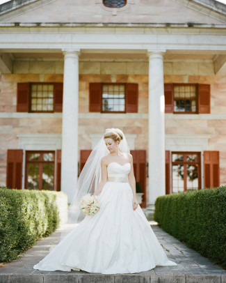 Bride in ball gown wedding dress standing in front of Tate House Mansion