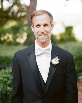 Groom wearing black tux with white bow tie and boutonniere