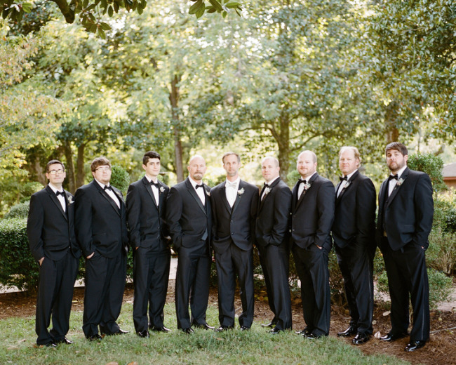 Groom standing with groomsmen all in black tux for outdoor wedding at Tate House Mansion