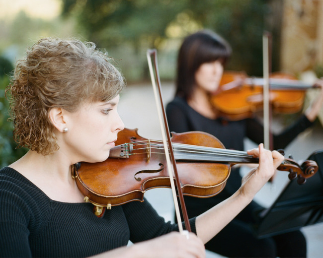 String duo playing violins in outdoor wedding