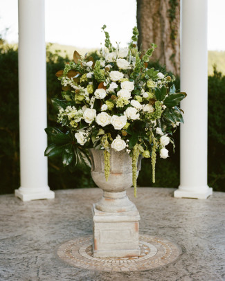 Beautiful urn of white flowers and green foliage for elegant outdoor wedding ceremony