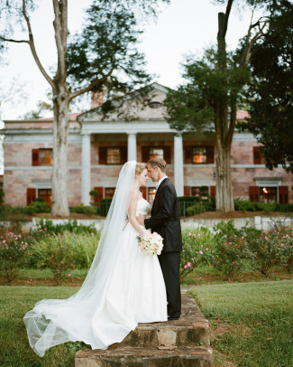 Bride and groom head to head standing in front of Tate House Mansion