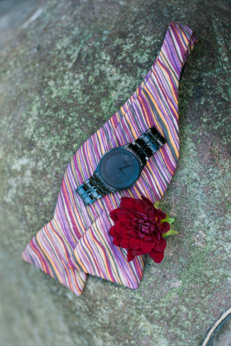 Multi-colored striped bow tie with black watch on top