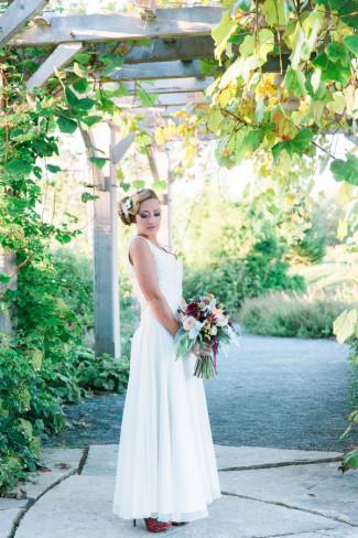 Model bride holding bouquet under arbor at Boothbay Botanical Gardens