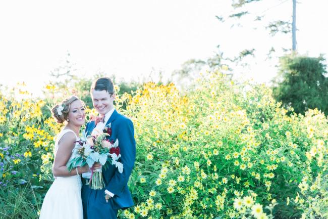 Bride and groom standing in garden of Boothbay Botanical Gardens