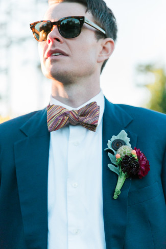 male model wearing sunglasses, striped bow tie, and boutonniere
