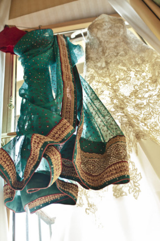 Green Saris with a white wedding dress hanging in the window for an Indian bride