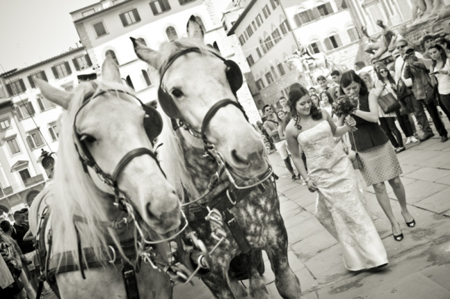 Bride and mother of the bride walking toward town hall in Florence after a horse drawn carriage ride