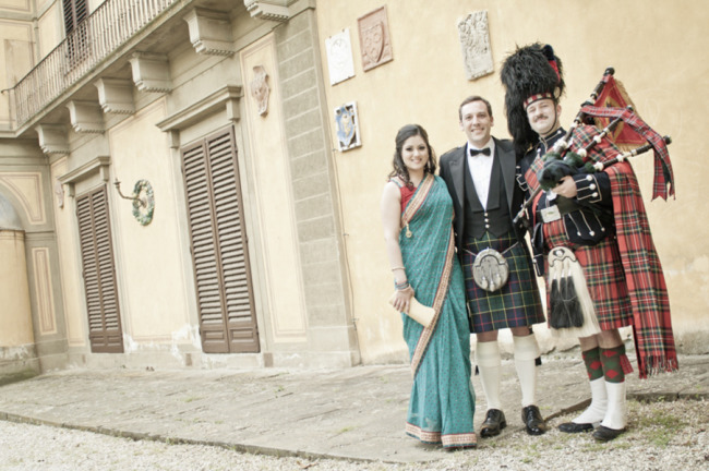 Indian Bride and Scottish groom standing with bagpiper