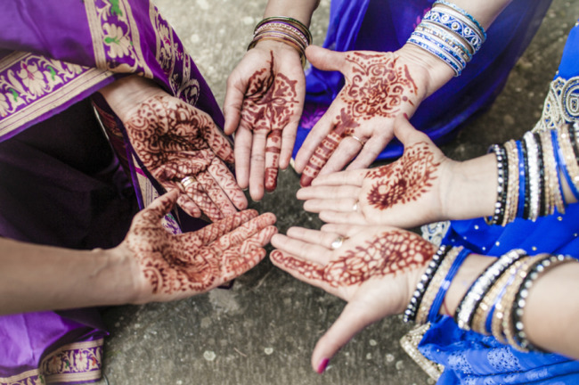 Bride with bridesmaids with henna all over their hands for wedding ceremony