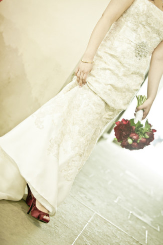 Bride wearing strapless dress with red heels and holding a red bouquet