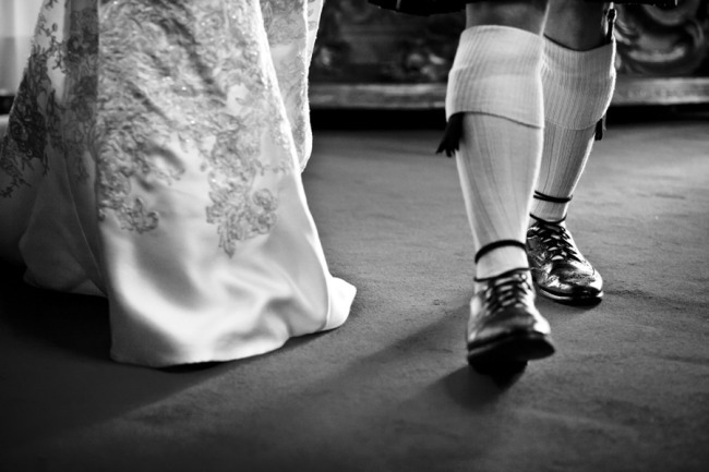 Bottom of a brides wedding dress and groom wearing traditional Scottish shoes and socks