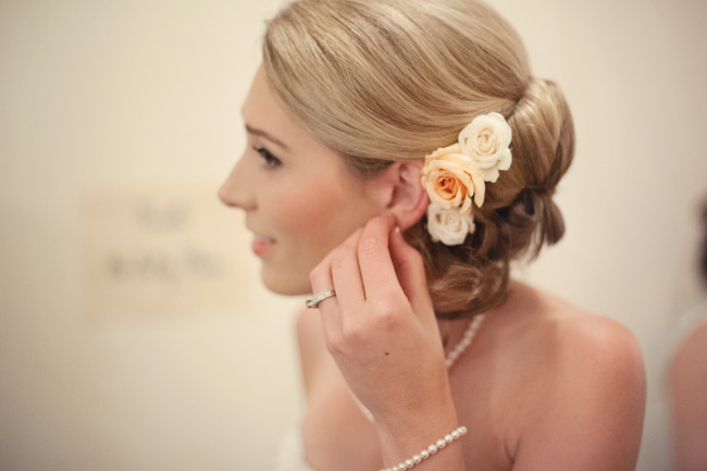 Bride wearing 3 cream roses in her hair that is in a bun
