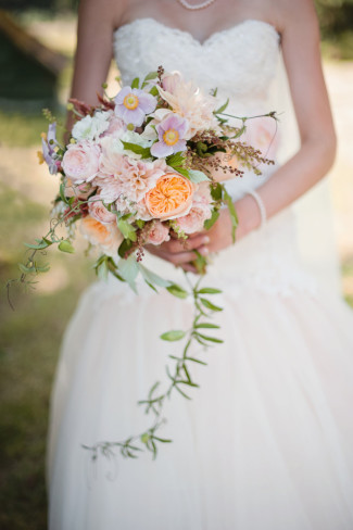Bride wearing a sweetheart neckline David Tutera gown holding a tropical loose floral bouquet