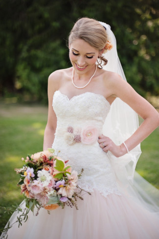 Bride wearing David Tutera gown and soft pink sash belt with flowers