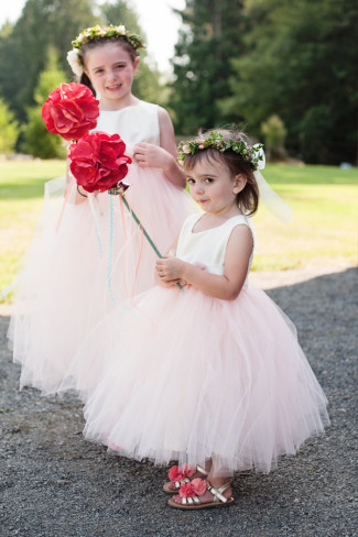flower girls in light pink dresses with giant red flower wand