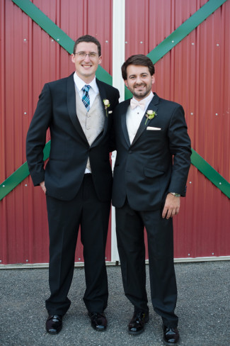 groom and groomsman in front of red barn door at Farm Kitchen