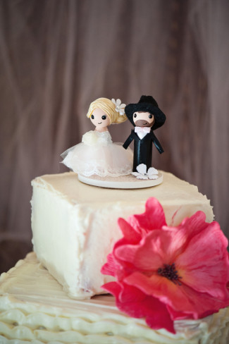 2 tier square wedding cake with pink flower and wooden bride and groom cake toppers
