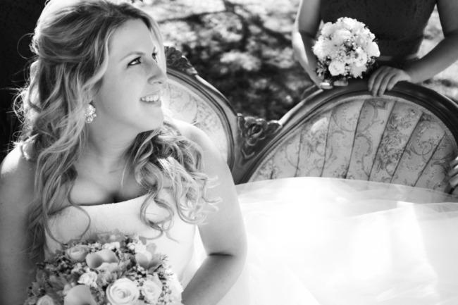 Black and white photo of Bride sitting on vintage sofa