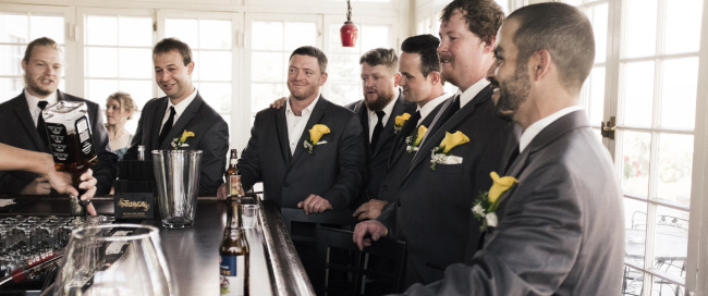 Groom and groomsmen all in grey suits and yellow Lilly boutonniere standing around the bar