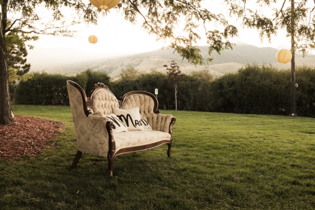 Vintage sofa in a field of the manor house with yellow paper lanterns hanging from the trees