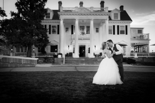 Bride and groom kissing on front lawn of the manor house in Colorado