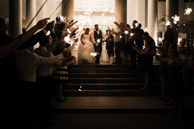Bride and groom walking down steps for their send off of The Manor House while guests have sparklers