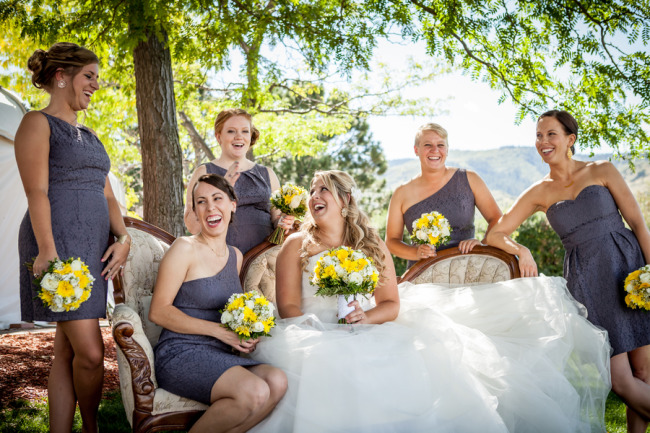 Bride laughing with bridesmaids who are wearing mismatched grey dress standing outside