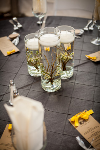 Tall clear glass vases with water and floating candles for wedding reception center pieces