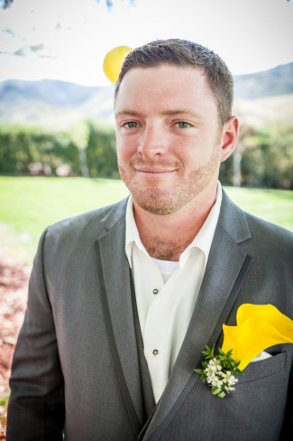 Groom wearing grey tux with no tie and a yellow Lilly boutonniere