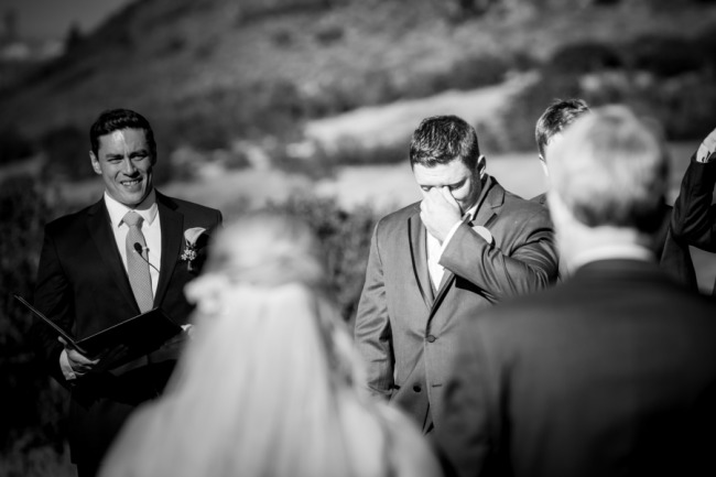 Black and white photo of groom crying as bride walks down the aisle in outdoor wedding ceremony