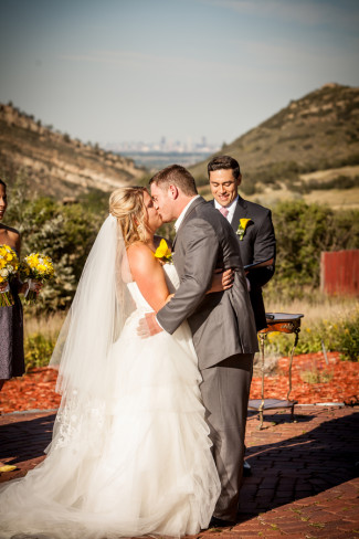 Bride and groom kissing during yellow and grey outdoor wedding ceremony