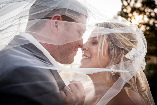 Bride and groom standing nose to nose under wedding veil