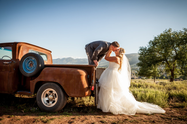 Groom standing in back of vintage truck bending over to kiss bride