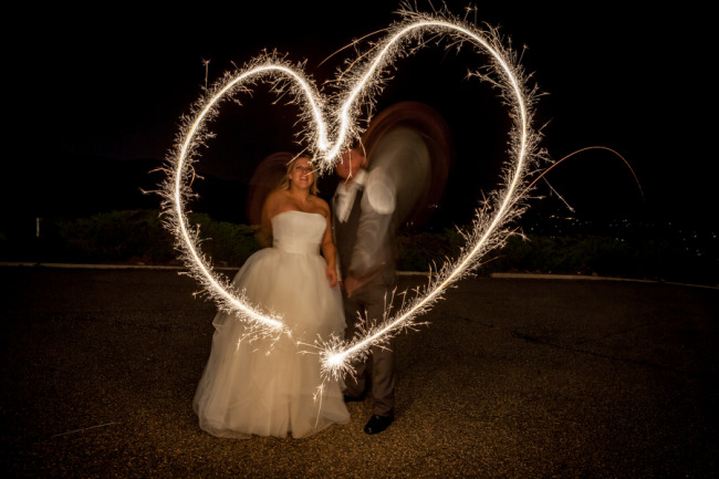 Bride and groom making a heart shape with their sparklers