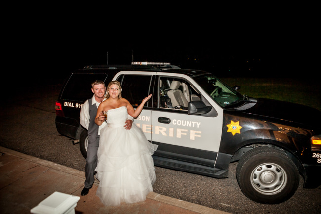 Bride and groom standing in front of a sherif truck