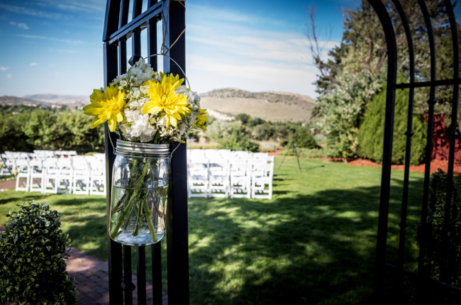 Garden archway with mason jar filled with white and yellow flowers for ceremony decor