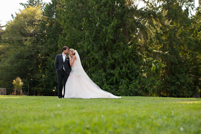 Bride wearing a David Tutera gown posing with groom in lawn.