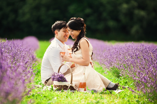 Engagement shoot in lavender field with couple drinking champagne