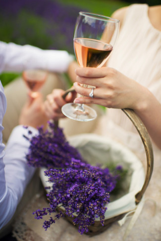 Women wearing a round diamond ring holding a glass of wine and basket of lavender
