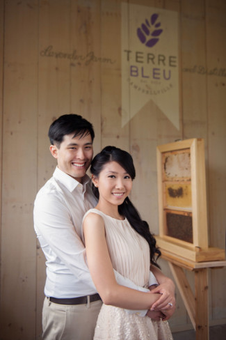 Engaged couple standing together in front of a honey bee house at Terre Blue farm