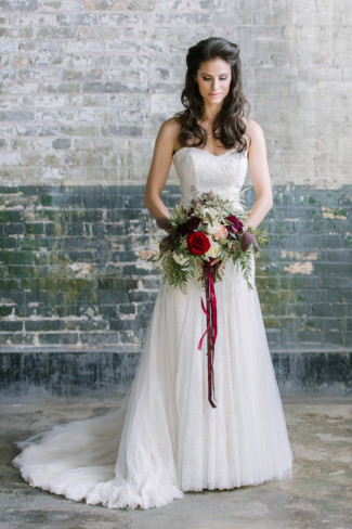 bride wearing sweet heart neckline holding loose bouquet with ribbons