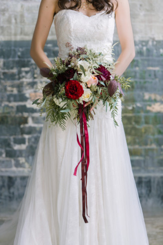 bride carrying a red, green peach and purple floral bouquet