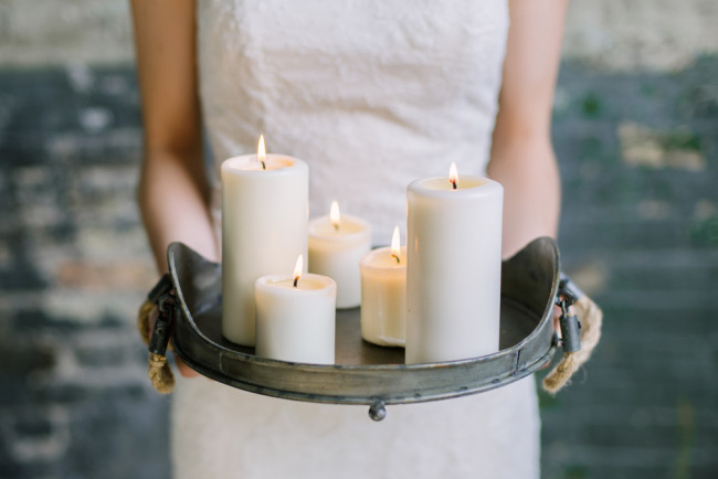 Bride carrying tray of candles
