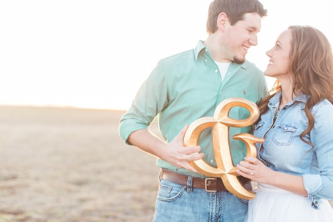 couple hold giant gold color ampersand