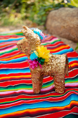 Gold pinata on a colorful Mexican blanket