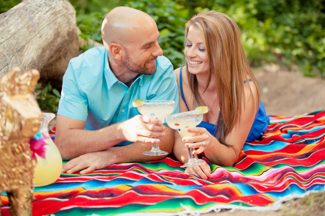 Engaged couple laying on a Mexican blanket clinking their margarita glasses together