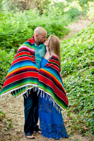 Engaged couple kissing wrapped with a colorful mexican blanket