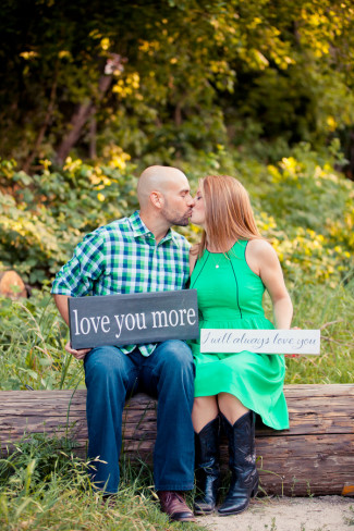 """Couple kissing on a log holding wooden signs saying """"love you more"""""""